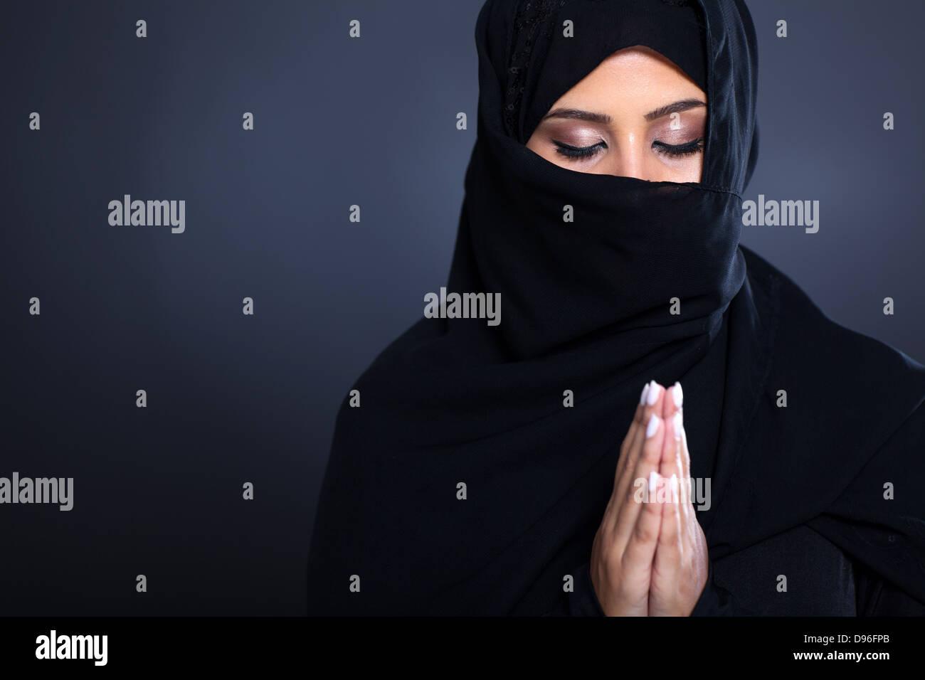Misteriosa mujer del Oriente Medio orando sobre fondo negro Imagen De Stock