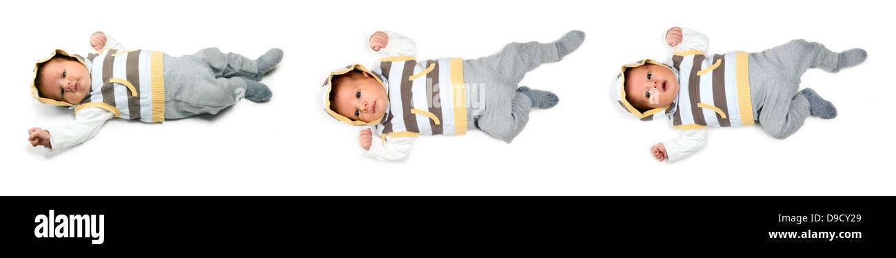 Hermoso bebé varón blanco con grandes ojos está mintiendo sobre fondo blanco. Imagen De Stock