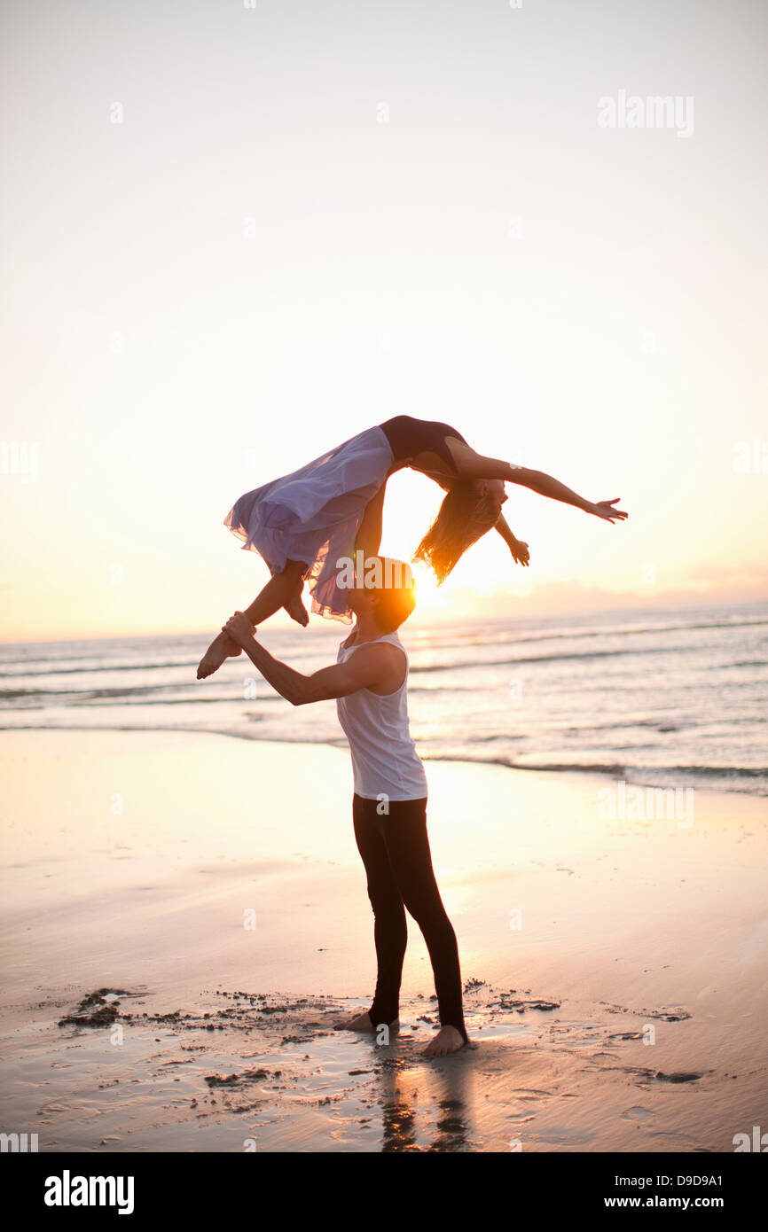 Joven pareja de baile de elevación en la soleada playa Imagen De Stock