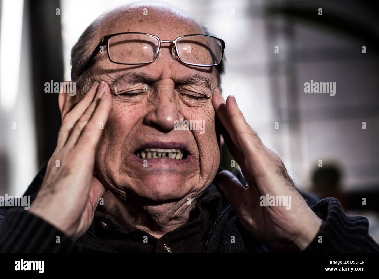 El hombre superior con los ojos cerrados, con gafas, que parecía estresado Imagen De Stock