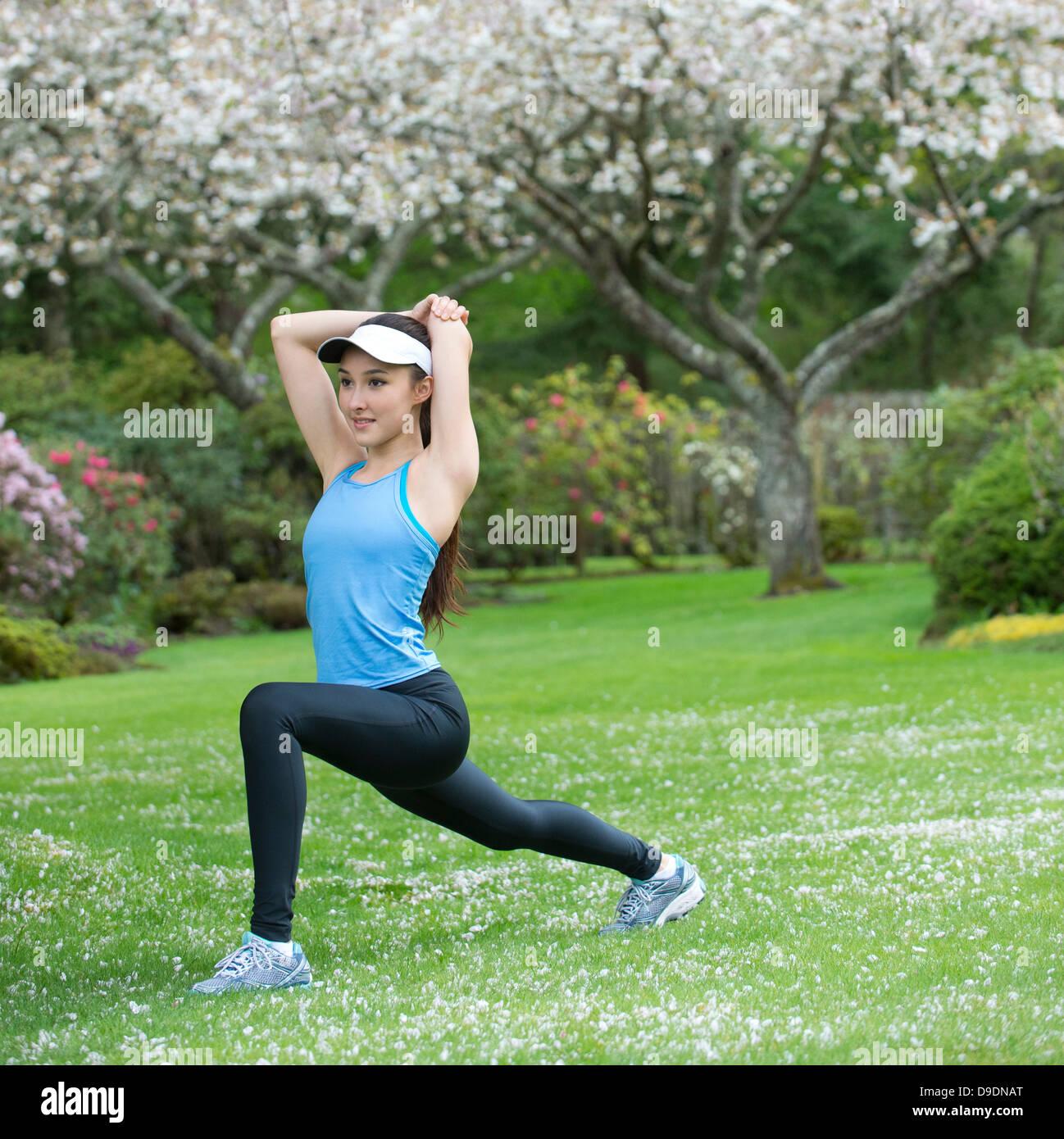 Adolescente vestido de azul sportswear estiramiento en park Imagen De Stock