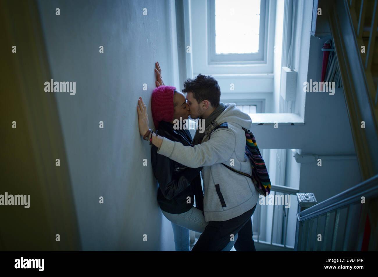Pareja joven abrazando en pasillo Foto de stock