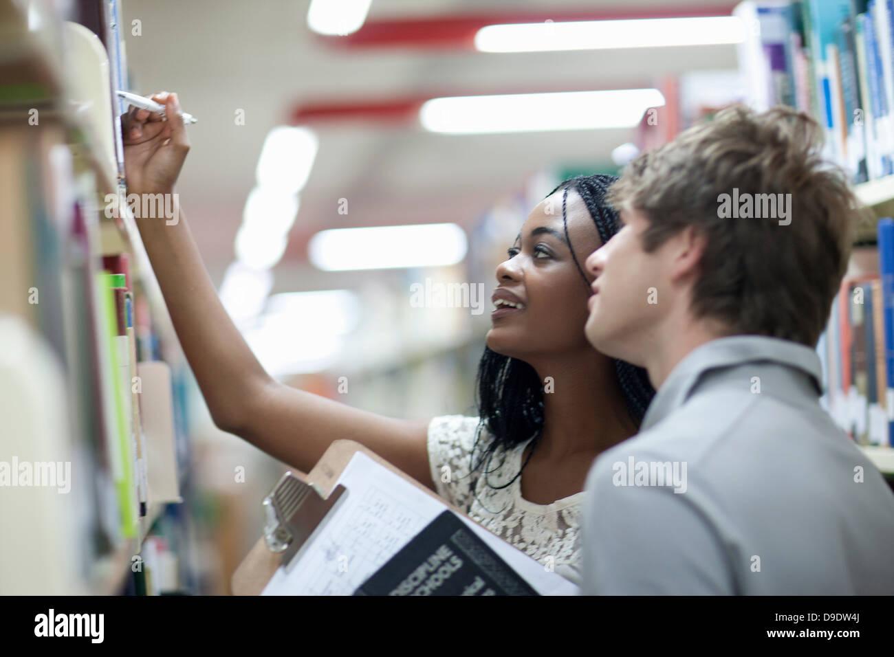 Los estudiantes que elijan los libros en la biblioteca Imagen De Stock