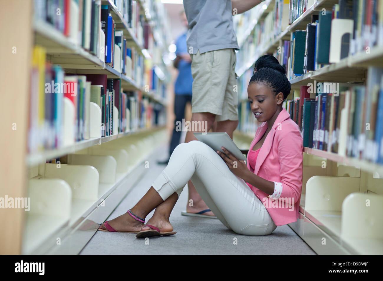 Estudiante sentado en el piso en la biblioteca utilizando una tableta digital Imagen De Stock