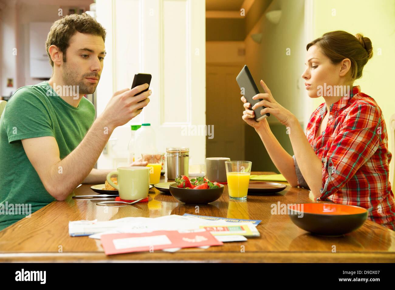 El hombre y la mujer mediante smartphone utilizando tablet digital en el desayuno Foto de stock