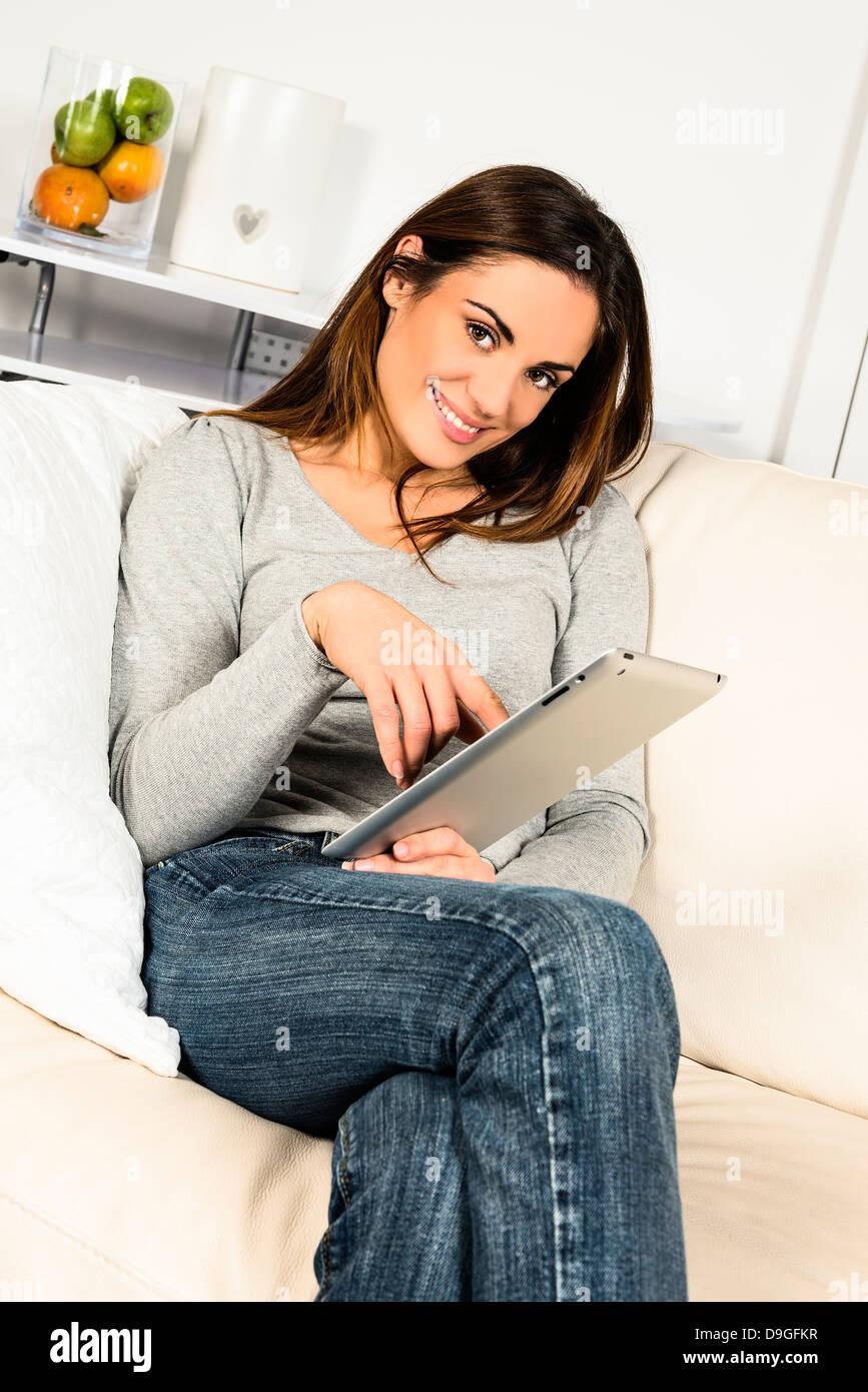 Mujer joven sentada en un sofá con almohadilla electrónica Imagen De Stock