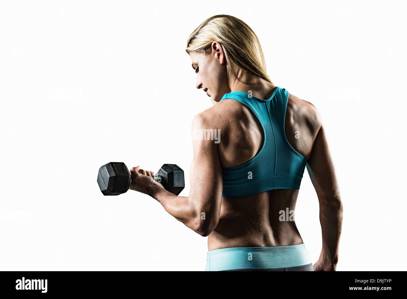 Mujer joven realizar flexiones de brazos (bíceps), Foto de estudio Imagen De Stock