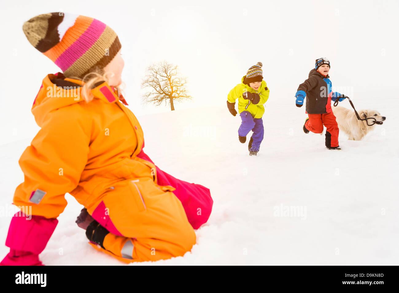 Dos niños corriendo en la nieve con el perro, niña arrodillada en primer plano Imagen De Stock