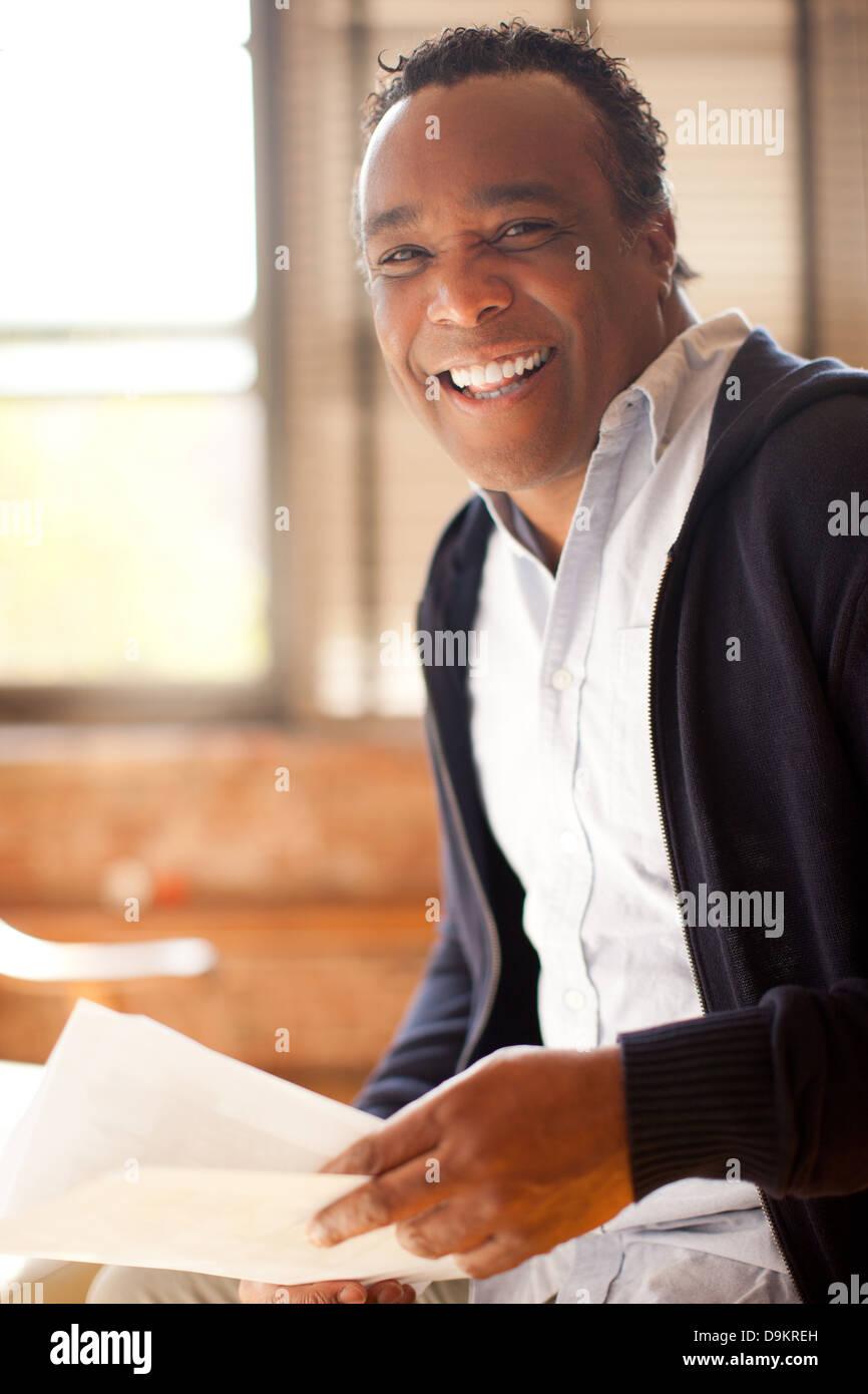 El hombre posando con sonrisa carismática y el aspecto de la felicidad Imagen De Stock