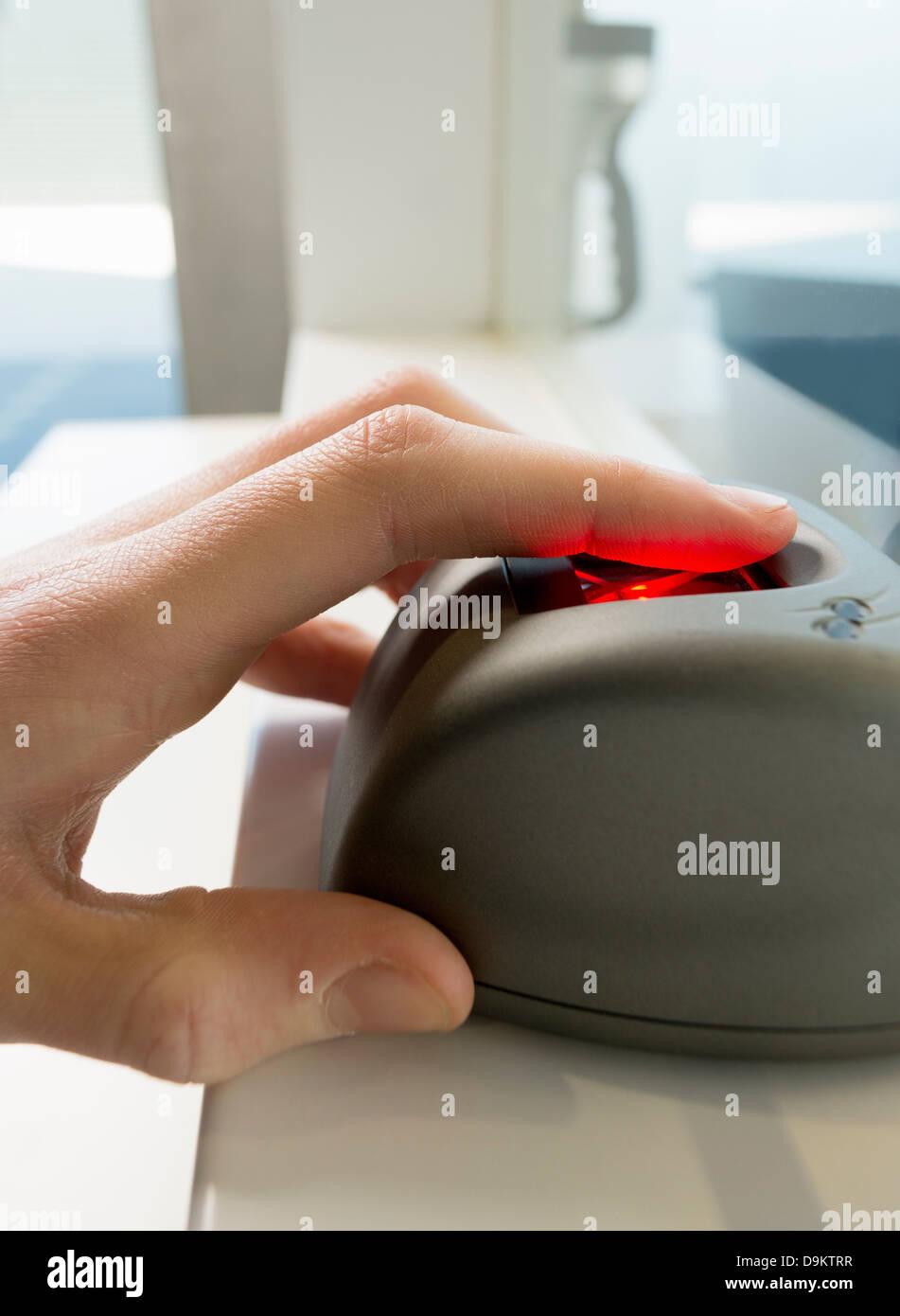 Con la mano en el dispositivo de reconocimiento de huellas dactilares Imagen De Stock