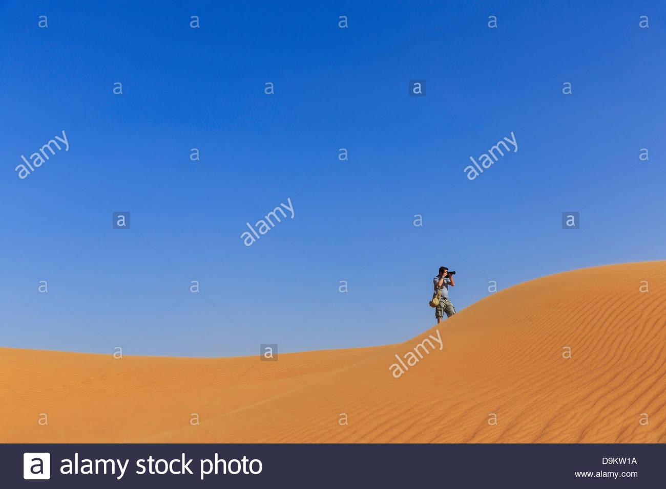 Hombre fotografiando en las dunas de arena en el desierto, Dubai, Emiratos Árabes Unidos. Imagen De Stock