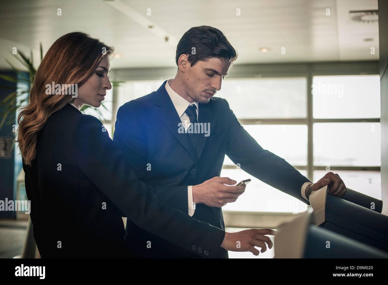 Los empresarios en el área de check-in del aeropuerto Foto de stock