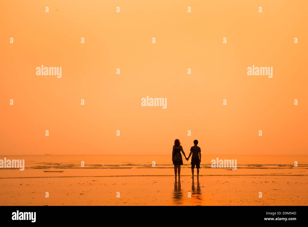 Sunset siluetas de pareja amorosa en la playa Foto de stock