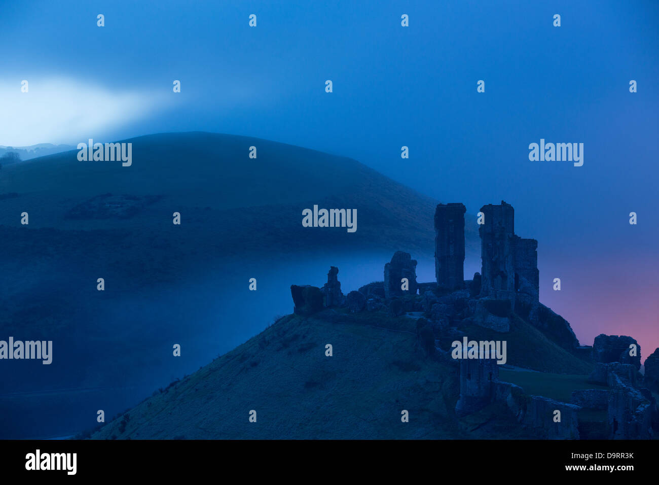 El castillo Corfe en la neblina al amanecer, Dorset, Inglaterra, Reino Unido. Imagen De Stock