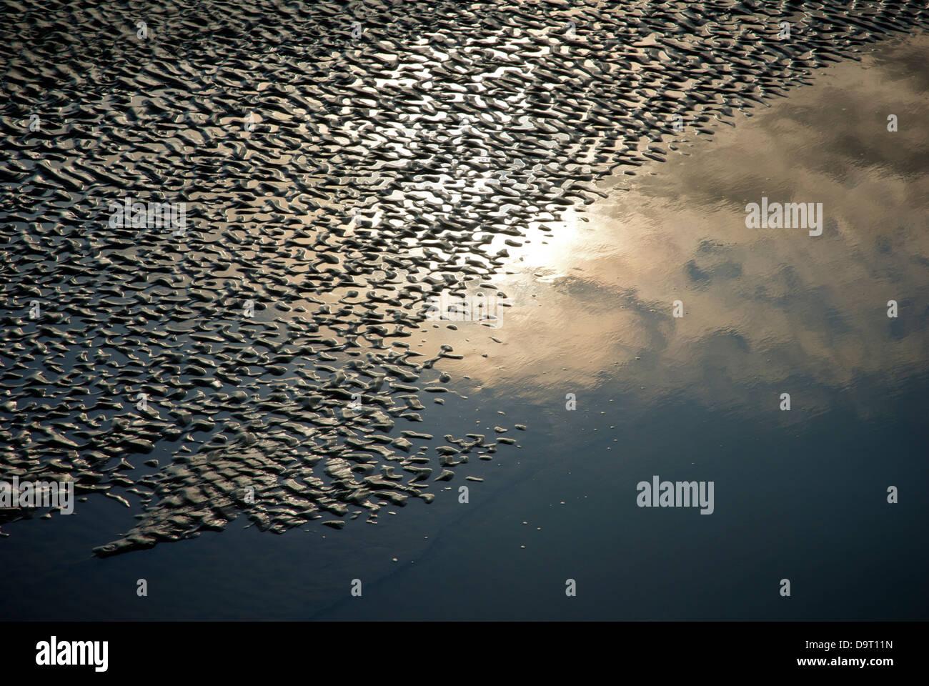 Puesta de sol reflejados en los patrones en una playa fangosa, Morecambe Bay, Cumbria, Inglaterra Imagen De Stock