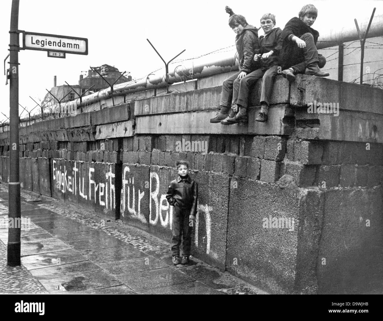 Un grupo de niños se sienta en el muro de Berlín en el 'Legiendamm' en el barrio de Kreuzberg Imagen De Stock