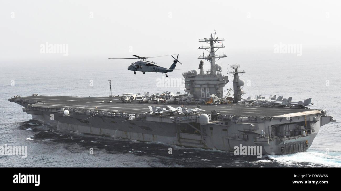 Marina de los EE.UU. MH-60S Sea Hawk helicóptero vuela por el portaaviones USS Nimitz, el 26 de junio de 2013 Imagen De Stock