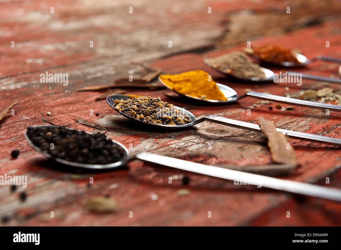 Cucharas de mesa colmado de diferentes especias sobre una superficie de madera con textura de color naranja. Utilización Foto de stock
