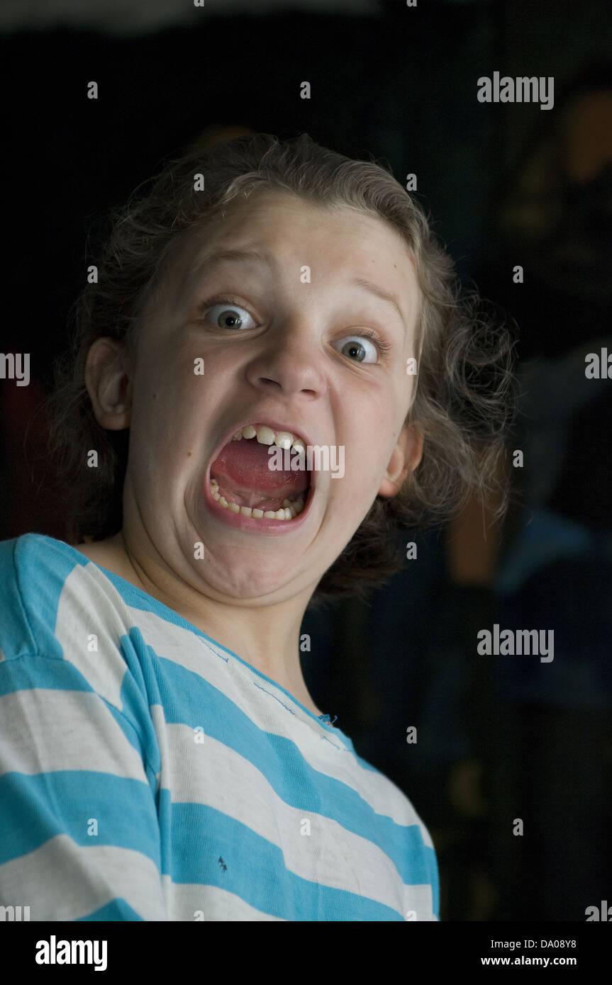 Retrato de una joven gritando con los ojos saltones y azul-blanco camiseta pelado Foto de stock