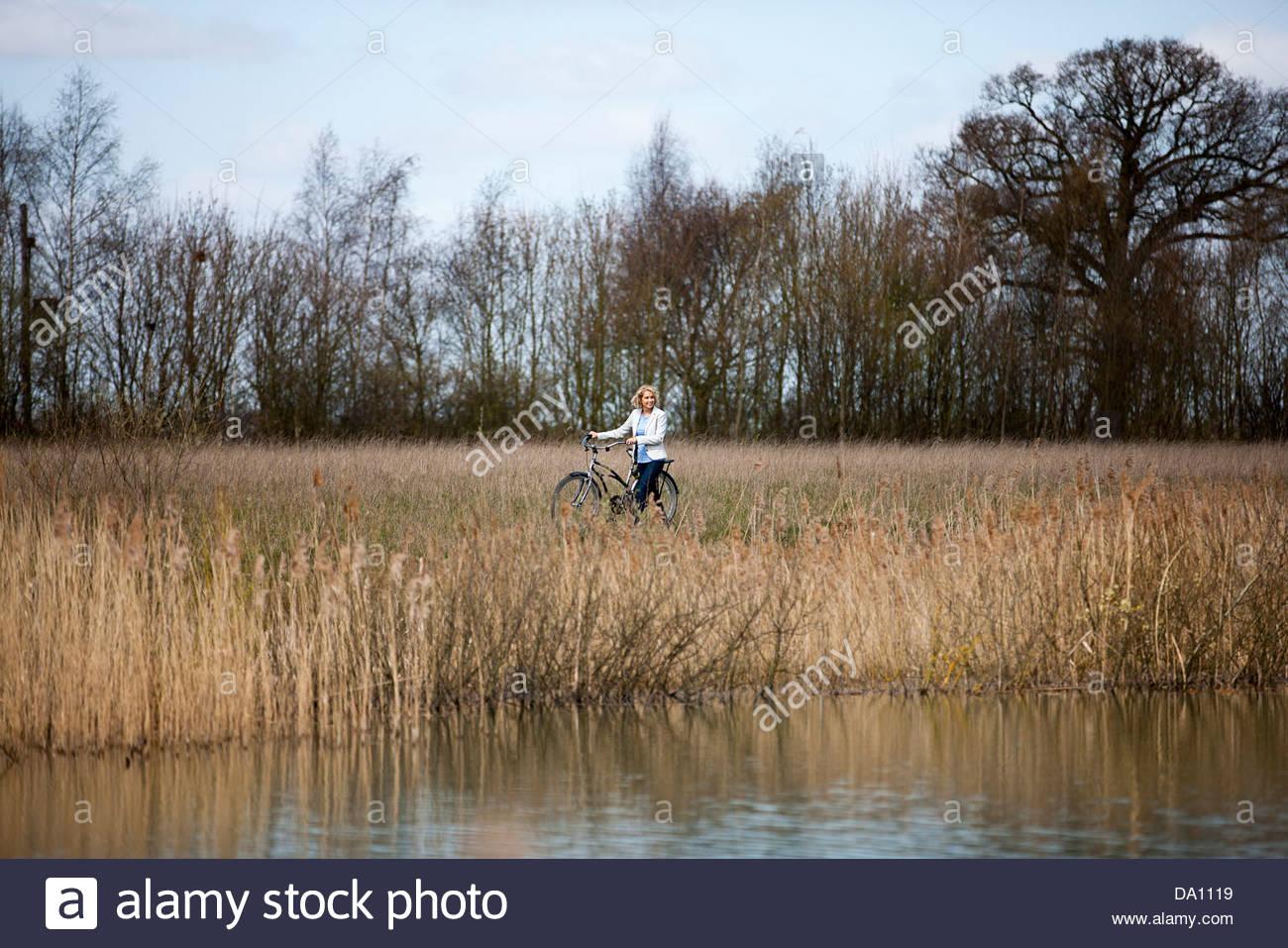 Una mujer madura empujando la bicicleta junto a un lago Imagen De Stock