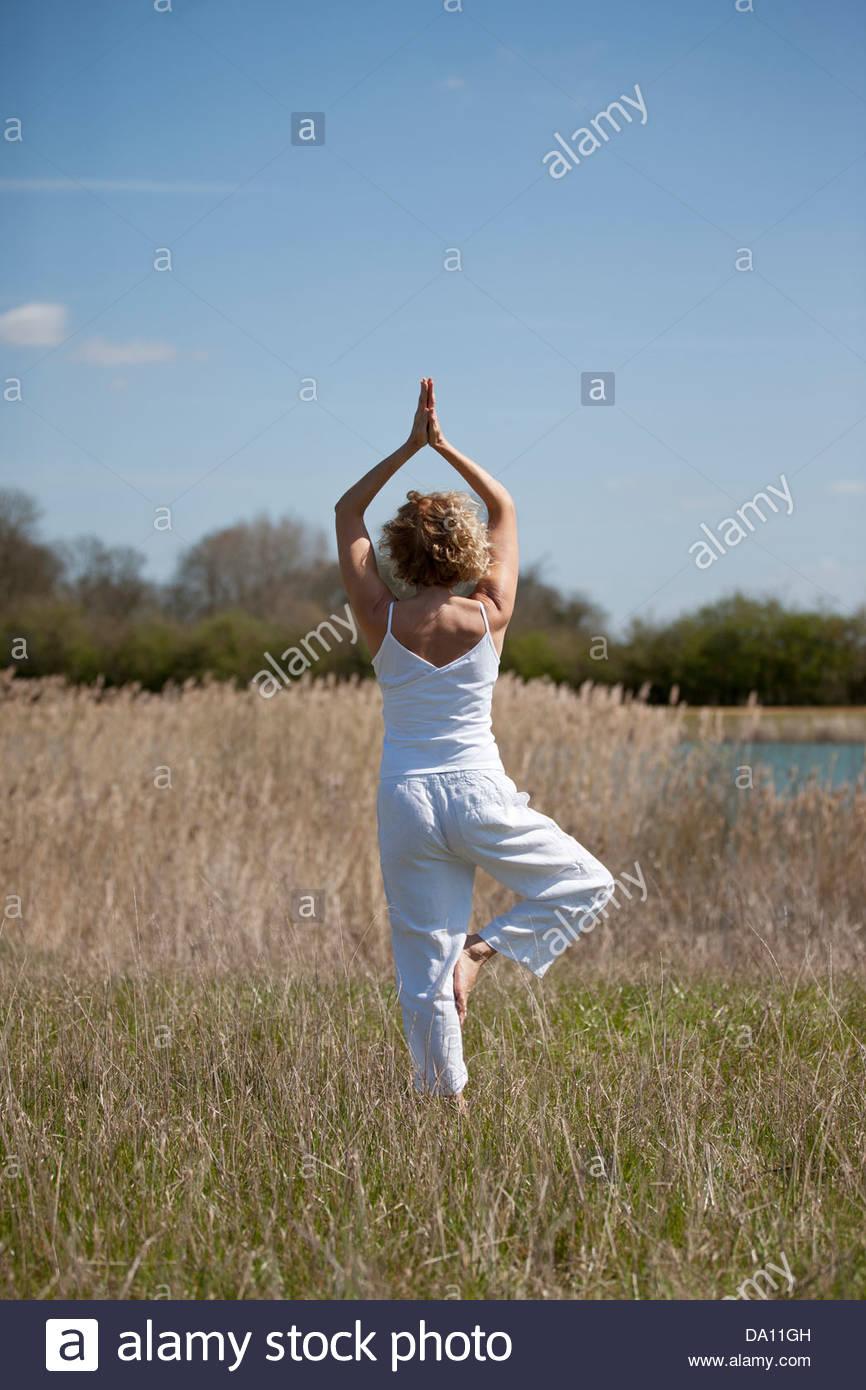 Una mujer adulta media practicando yoga en el campo en verano Imagen De Stock