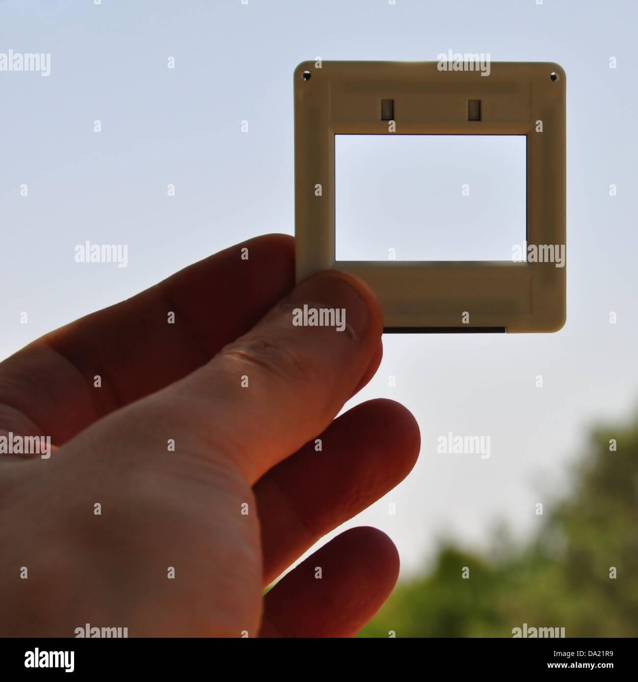 Mano con diapositiva fotográfica en blanco el marco de imagen. Coloque su propia imagen o texto. Foto de stock