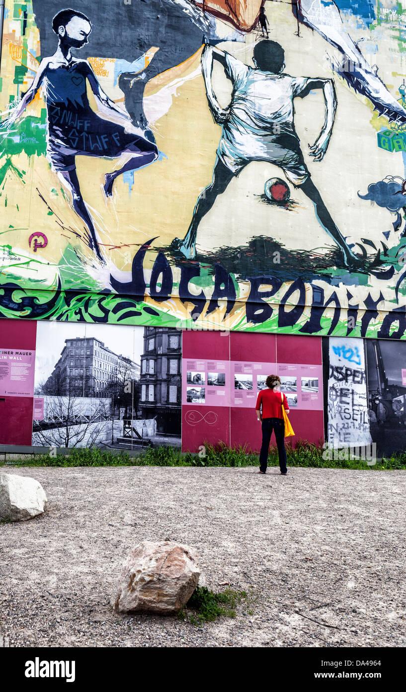 Mujer mirando al muro de Berlín memorial information board delante de una pared con Joga bonita (jugar maravillosamente) Imagen De Stock