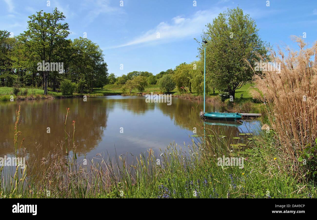 Tranquilo estanque con un pequeño barco en el muelle, Limousin, Francia Imagen De Stock