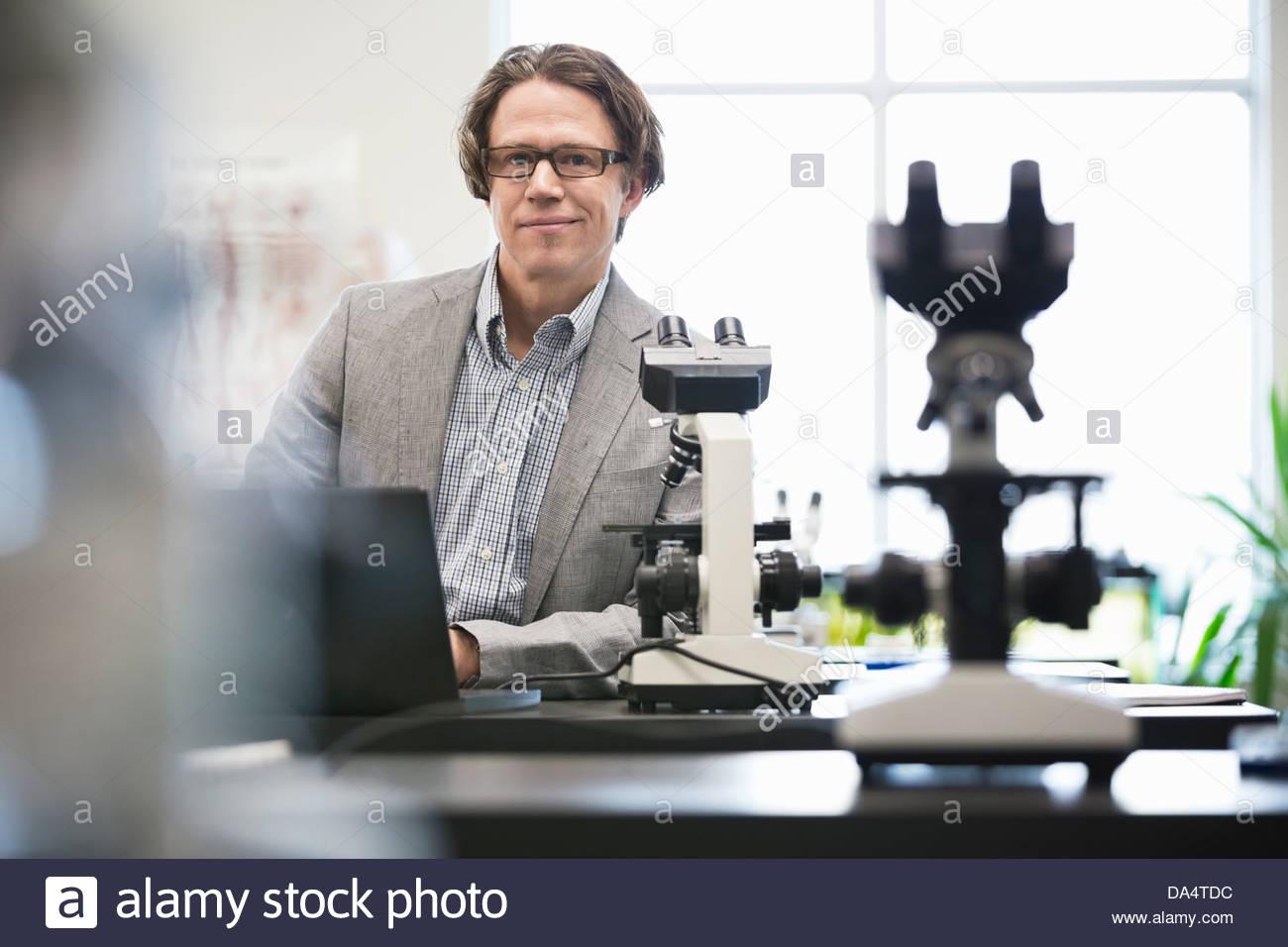 Retrato del profesor universitario masculino en la mesa inclinada en el laboratorio de ciencias Imagen De Stock