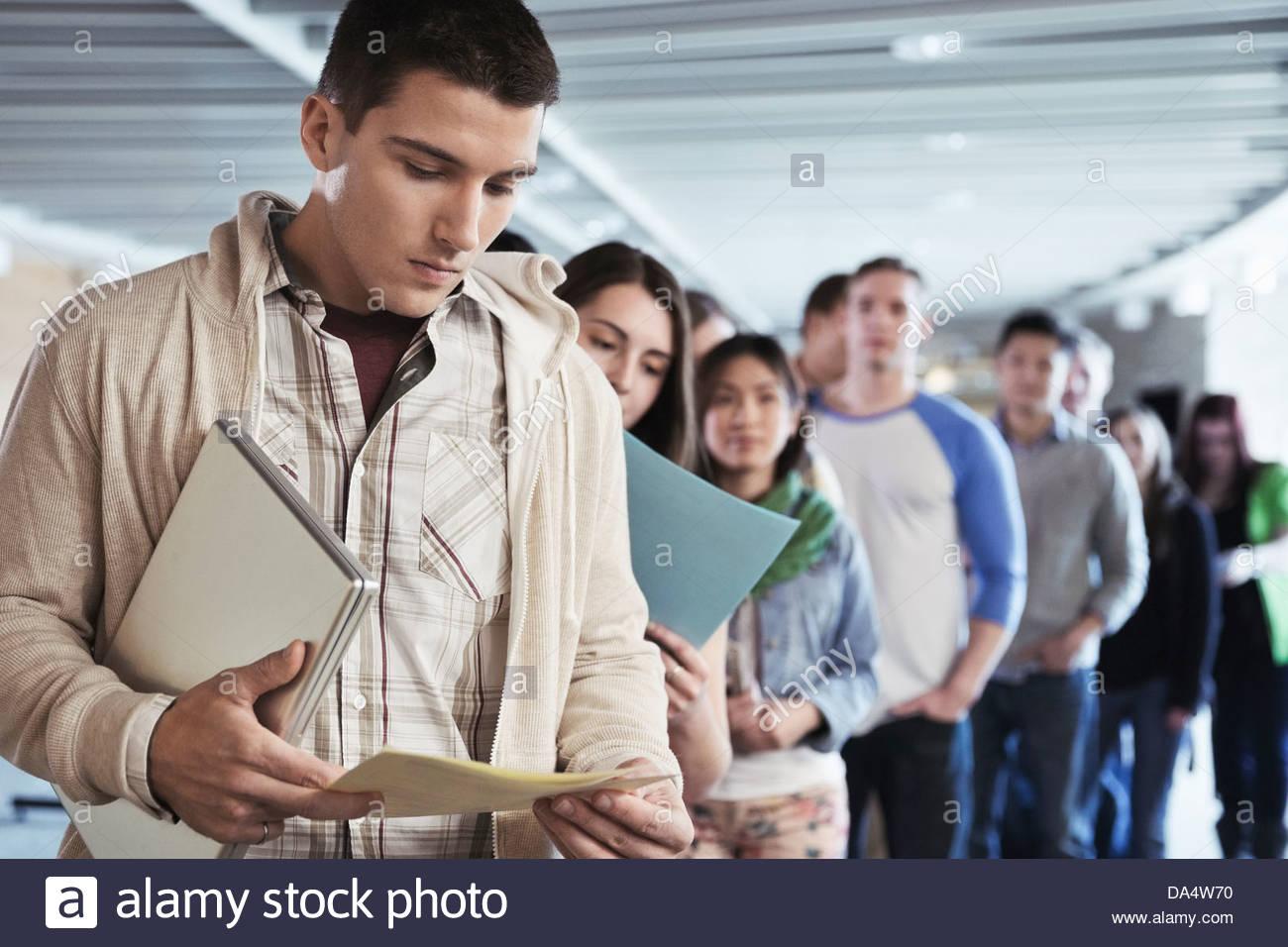 Gran grupo de estudiantes de pie en línea en campus universitario Foto de stock