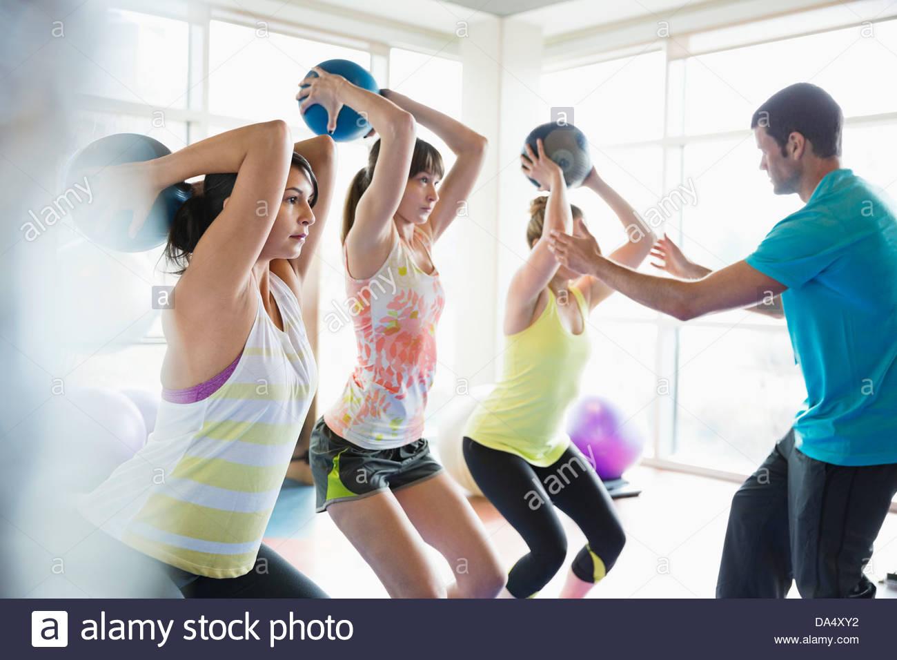 Las mujeres con pelotas medicinales en clase de gimnasia Imagen De Stock