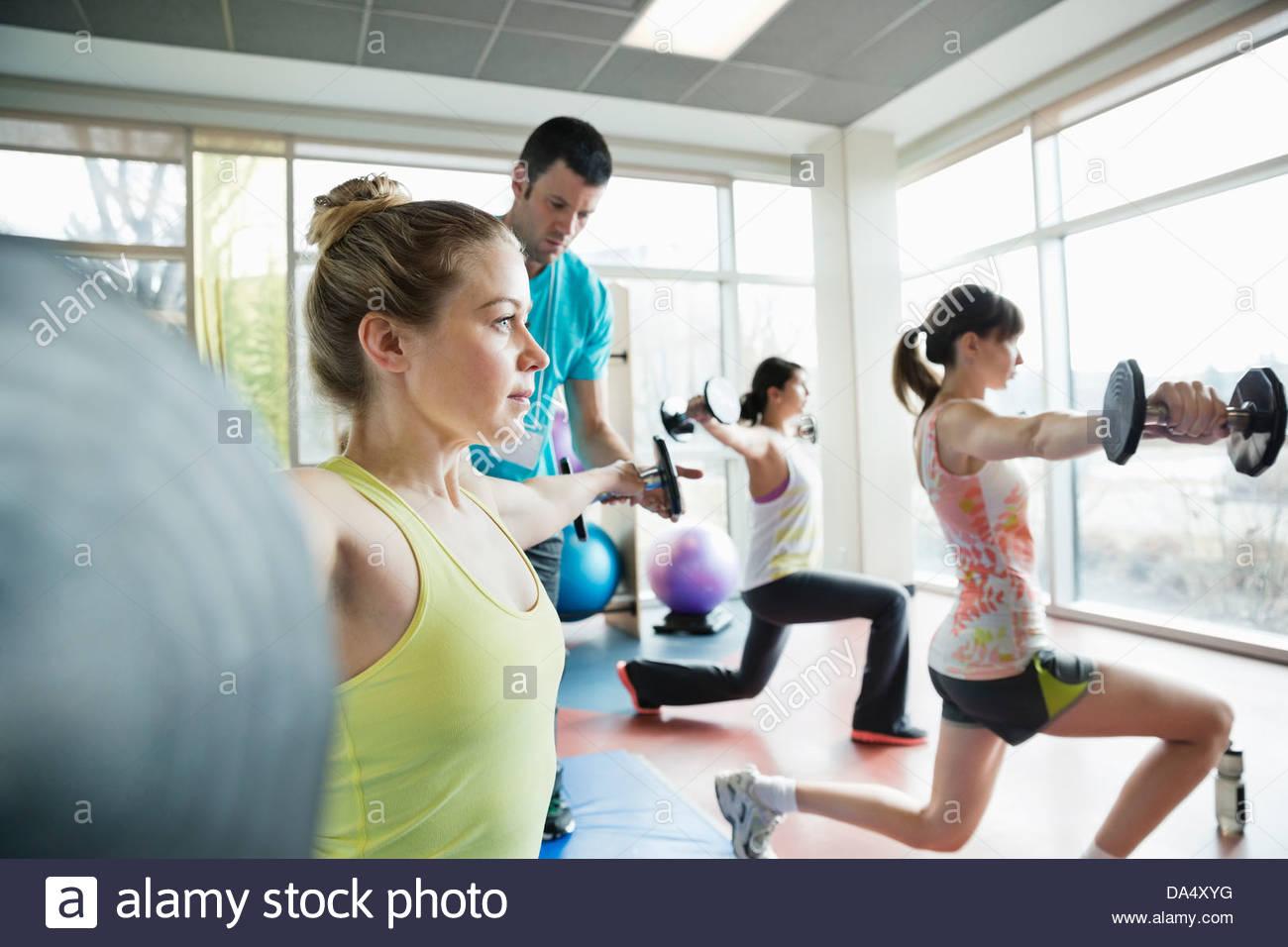 Instructor ayudar a mujer con ejercicio en clase de gimnasia Imagen De Stock
