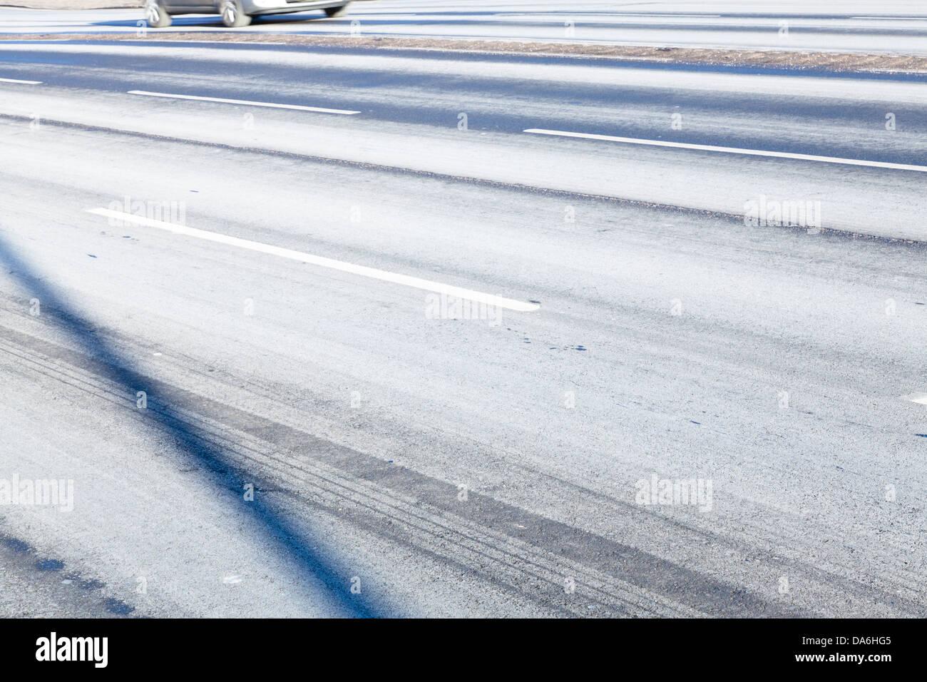 Visión abstracta de una calzada después del invierno salazón mostrando las sombras, marcas y marcas de neumáticos Foto de stock
