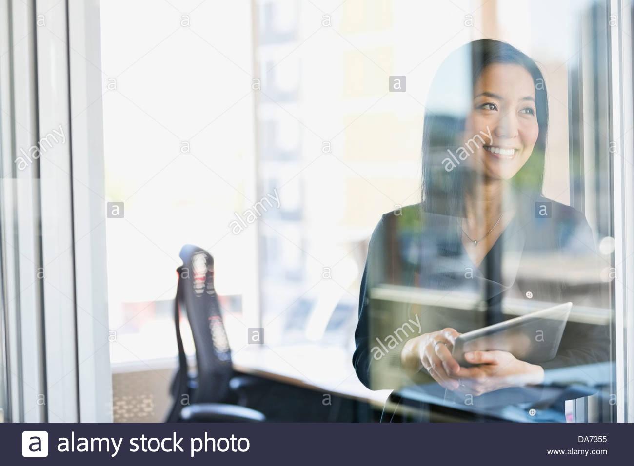 La empresaria sonriendo con tablet digital en Office Imagen De Stock