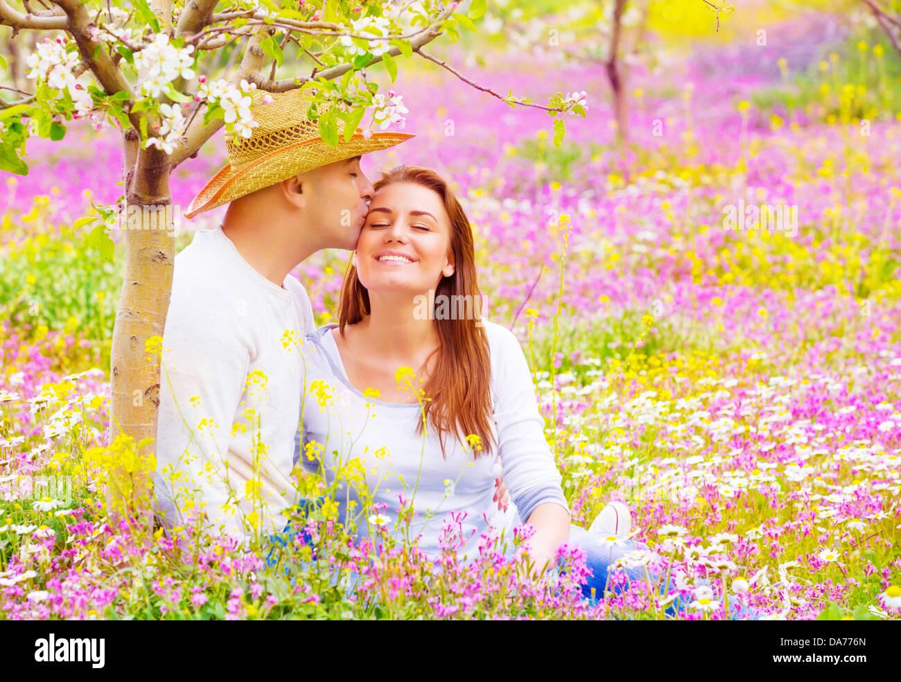 Los amantes felices besos al aire libre, cita romántica en el florido jardín, hermosa joven familia, cariño Imagen De Stock
