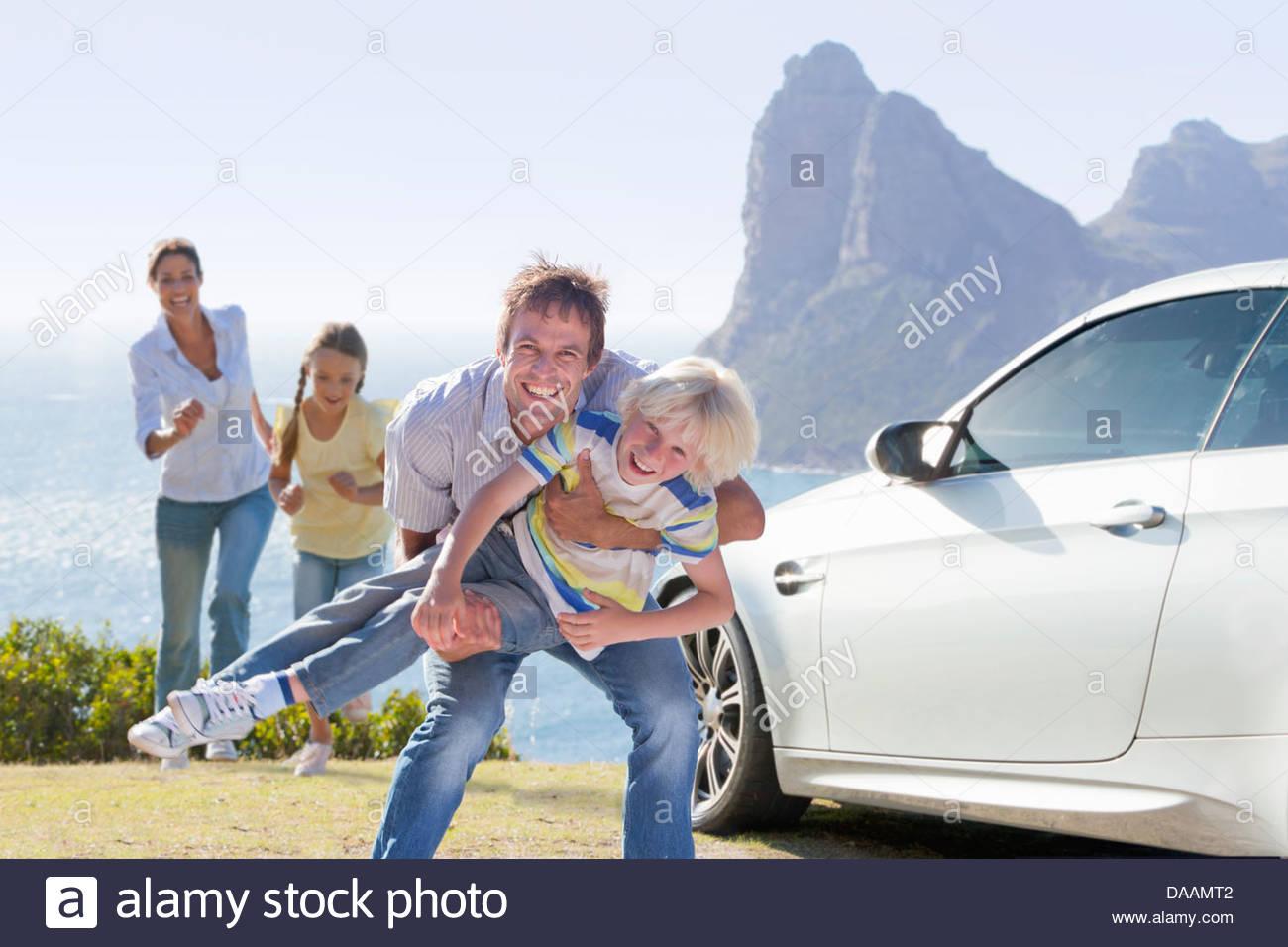 Retrato de familia lúdica fuera de coche cerca del mar Imagen De Stock