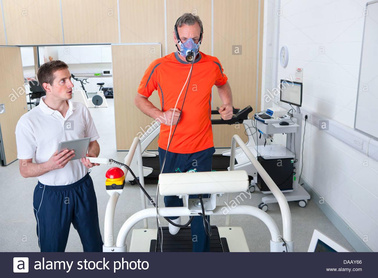 Deportes científico con supervisión de tableta digital runner con máscara en cinta en laboratorio Imagen De Stock