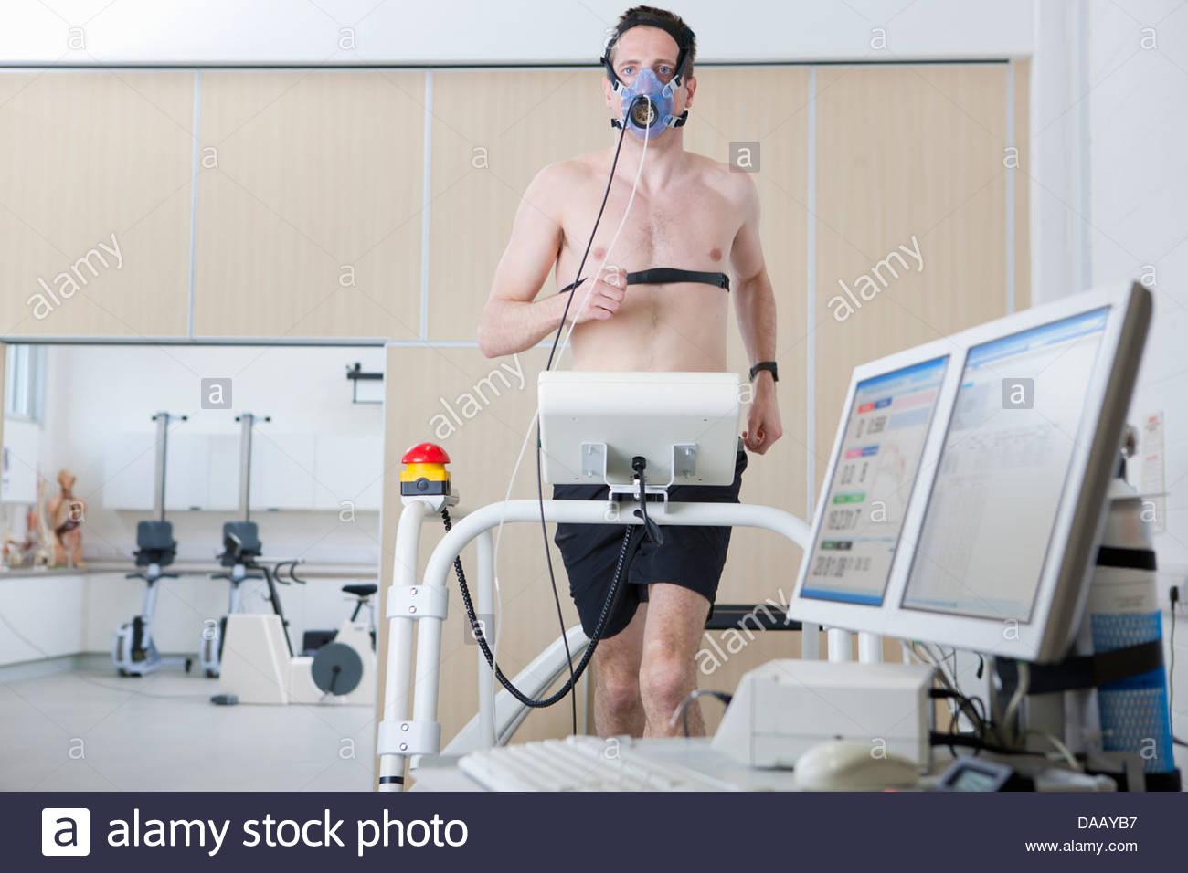 Runner con máscara en cinta en el laboratorio de ciencia de los deportes Imagen De Stock