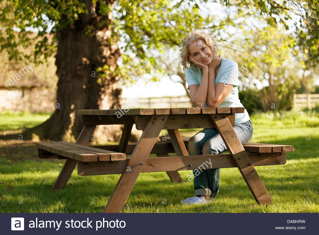Una mujer madura, sentado en un banco de jardín sonriente Imagen De Stock