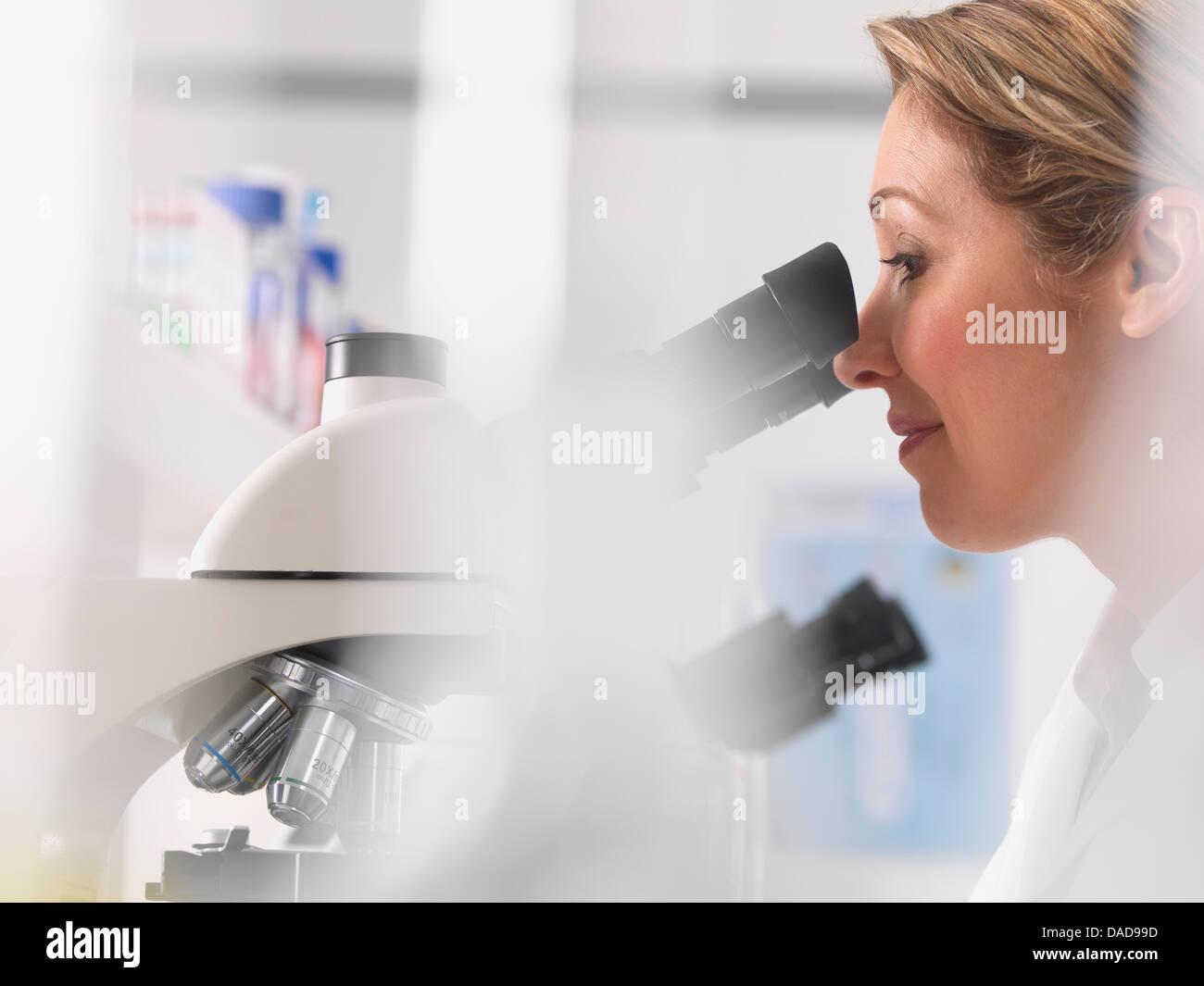 Microbiólogo hembra ver espécimen bajo el microscopio en el laboratorio Imagen De Stock