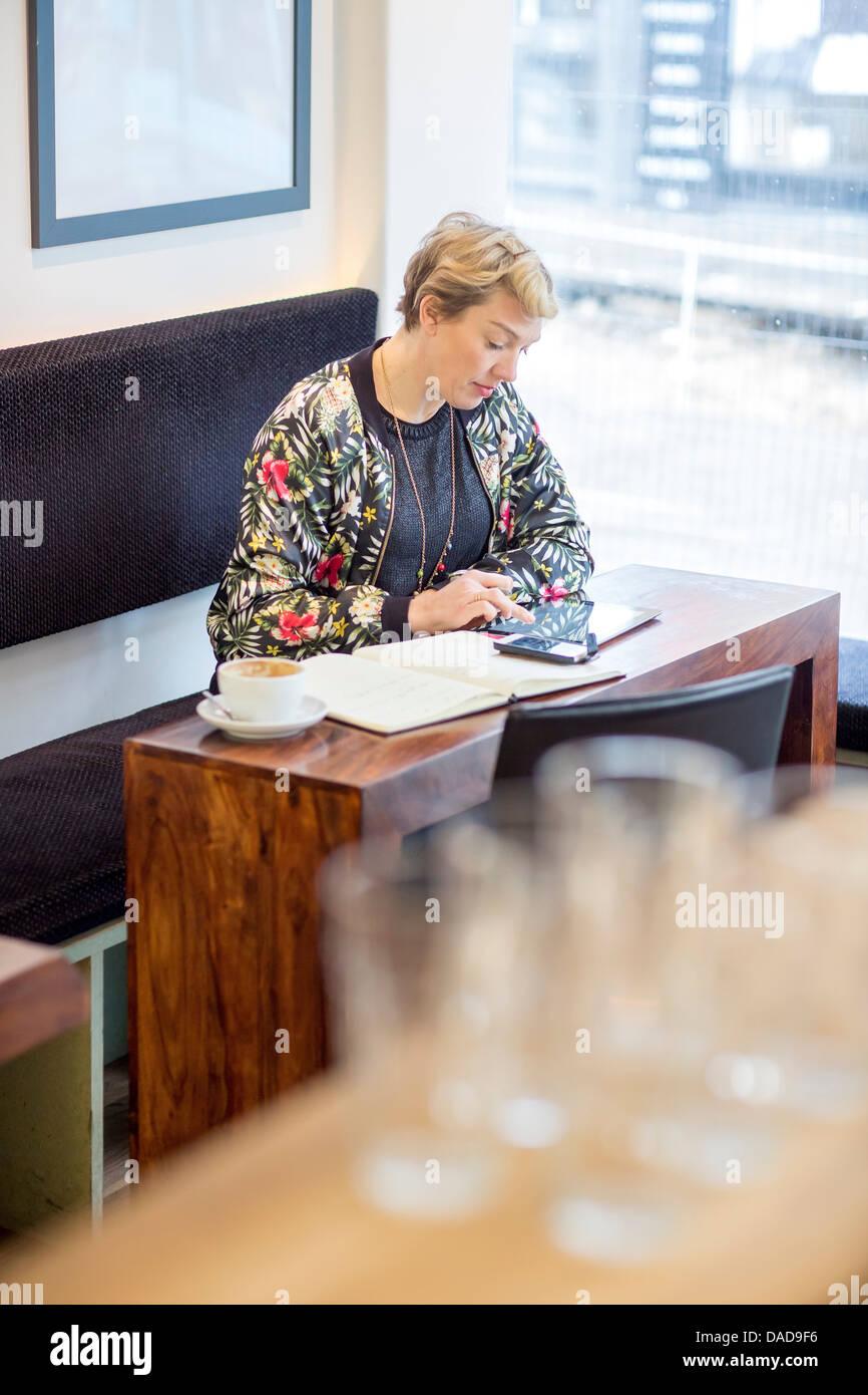 Mujer con digital comprimido en cafe Foto de stock