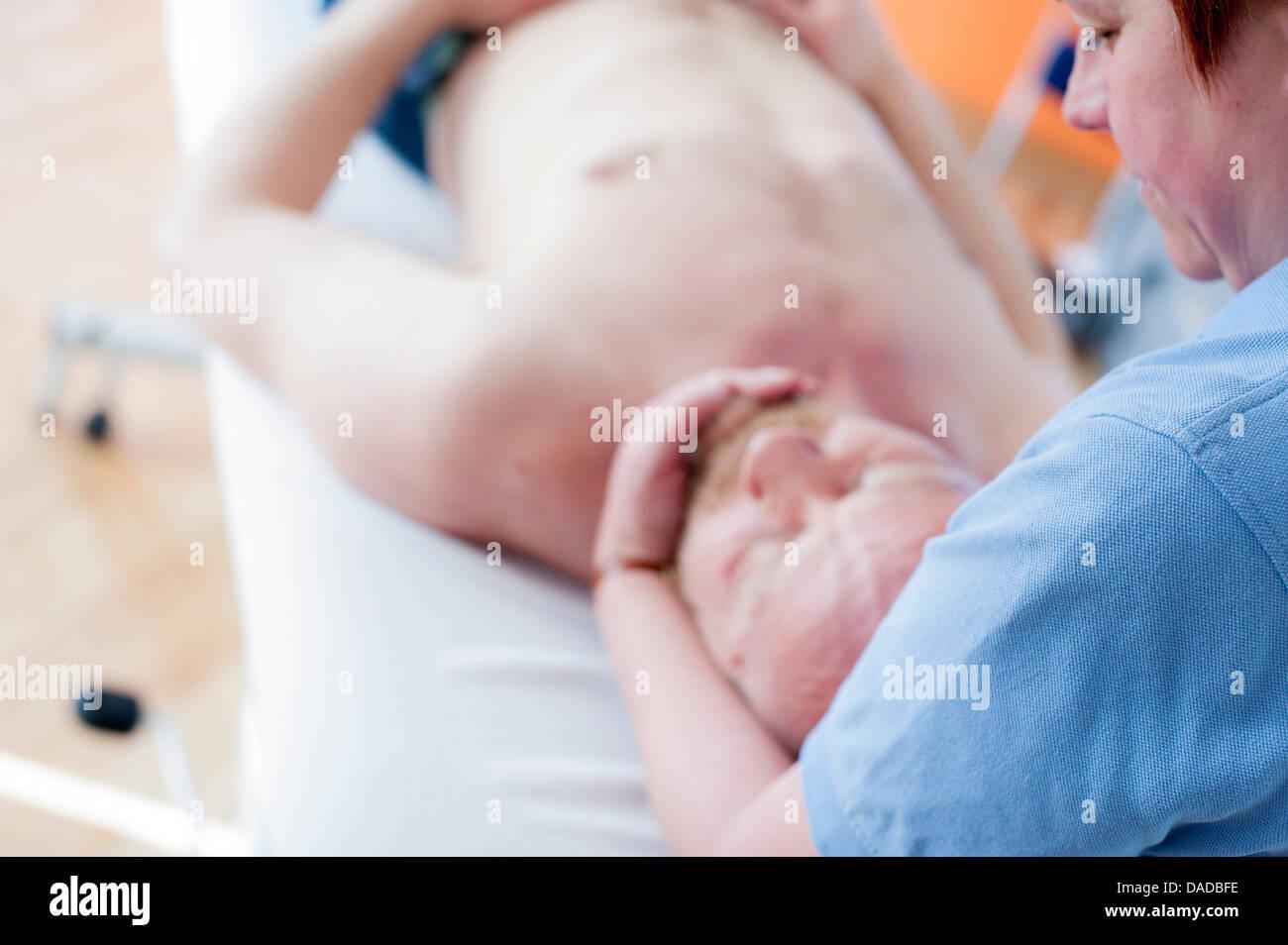 El hombre acostado sobre la espalda recibir masaje de cabeza Imagen De Stock