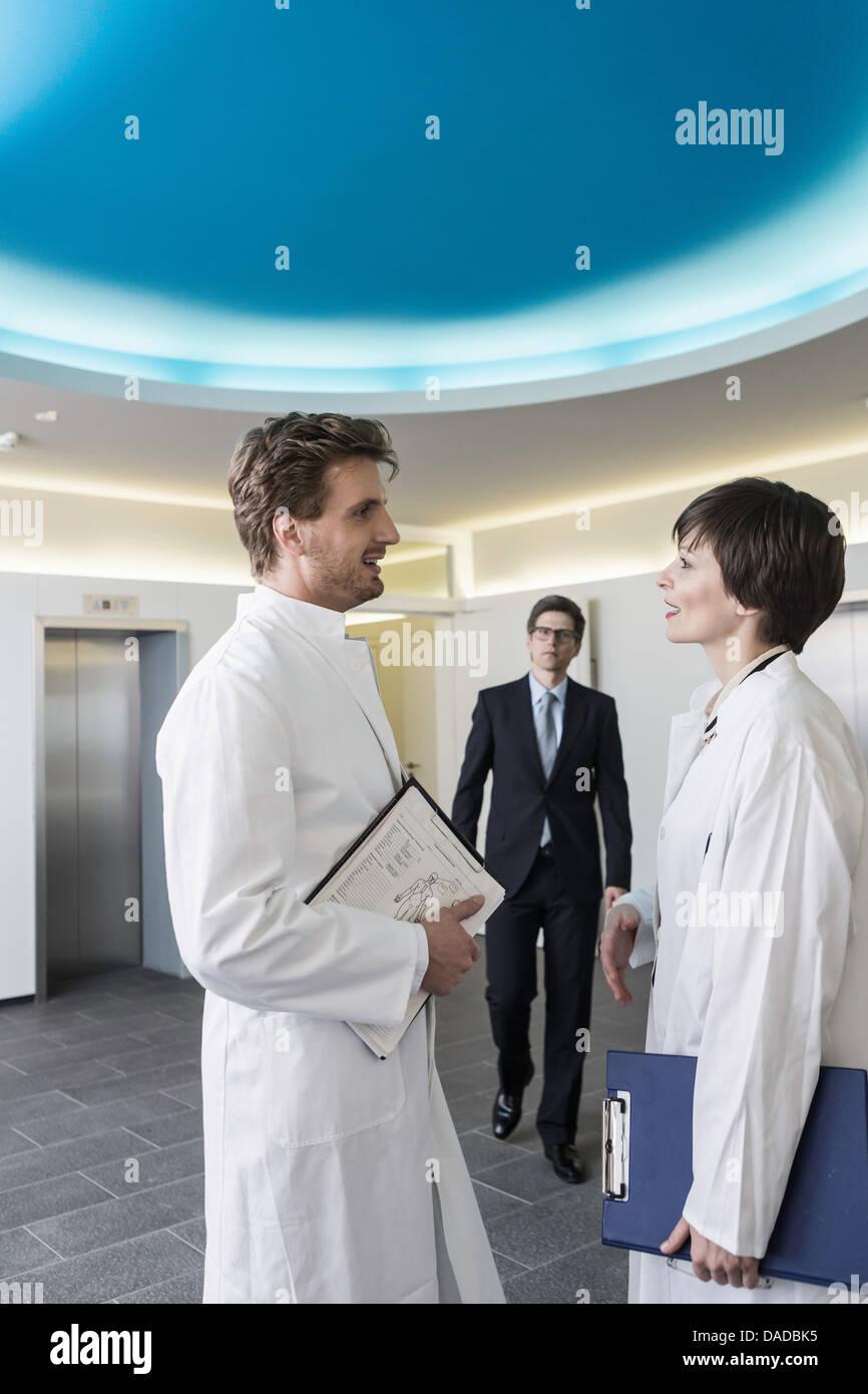 Hombre y mujer vistiendo batas de laboratorio tener conversación en el vestíbulo, el hombre vestido con Imagen De Stock