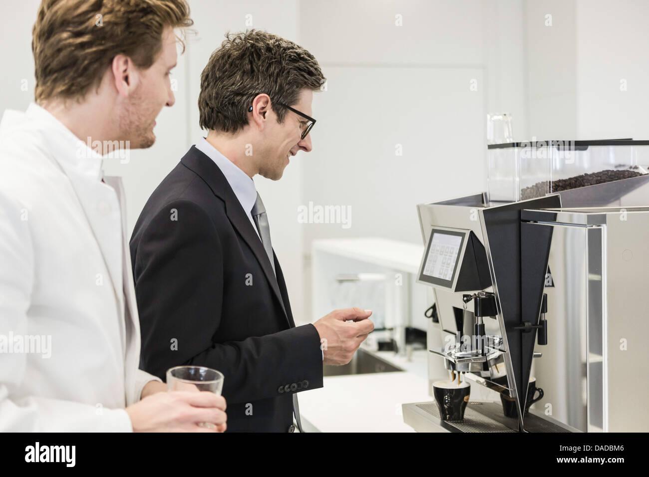 Hombre vestido con traje de negocios conseguir bebida de máquina de café Imagen De Stock