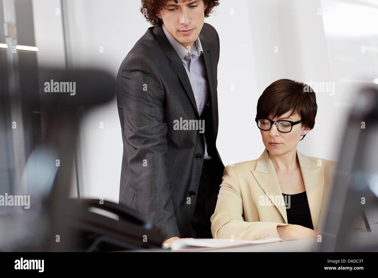 La empresaria sentados frente al escritorio, el hombre mirando por encima del hombro al papeleo Foto de stock