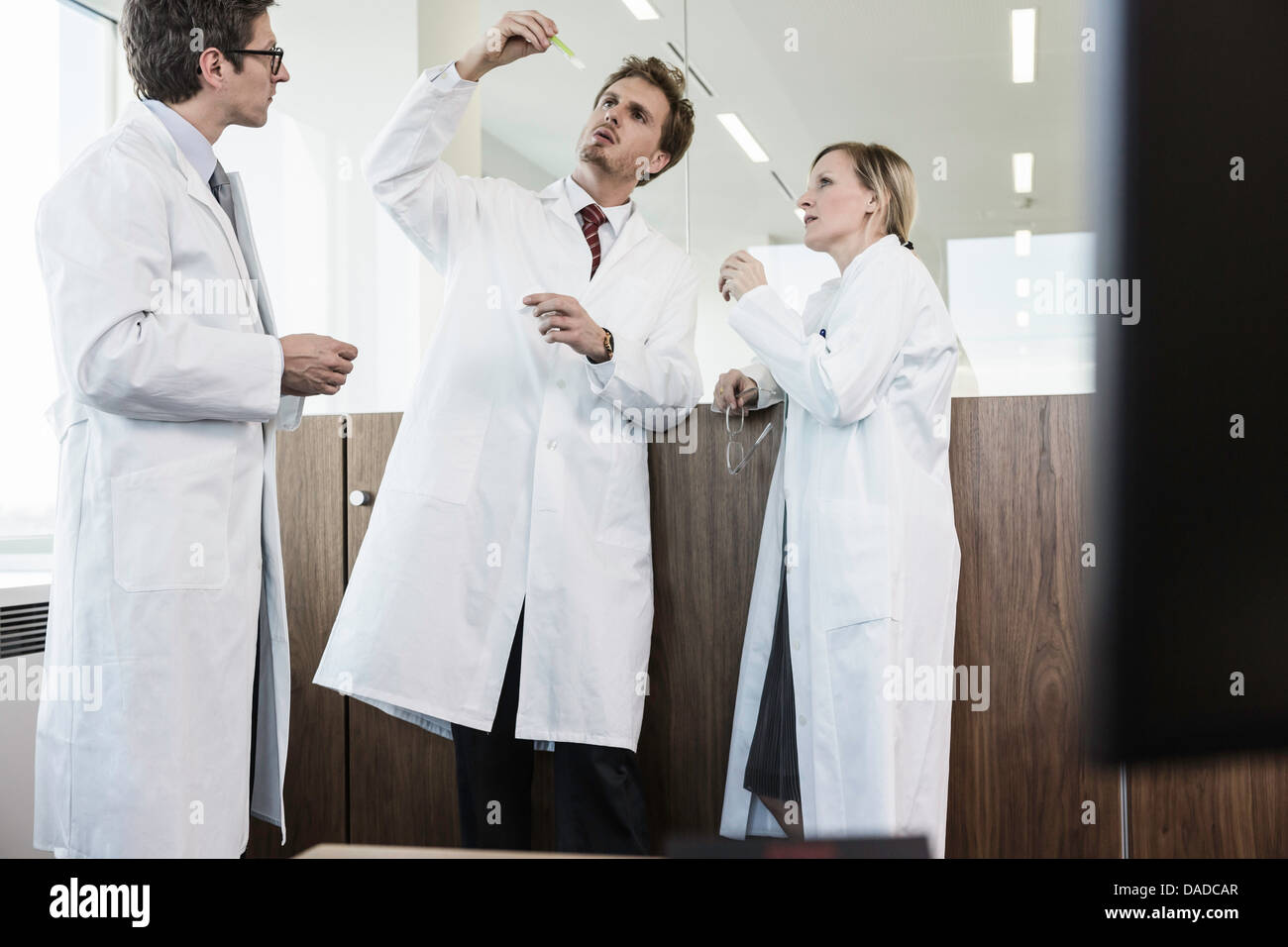 Tres personas vestidas con batas de laboratorio mirando a tubo de ensayo Imagen De Stock