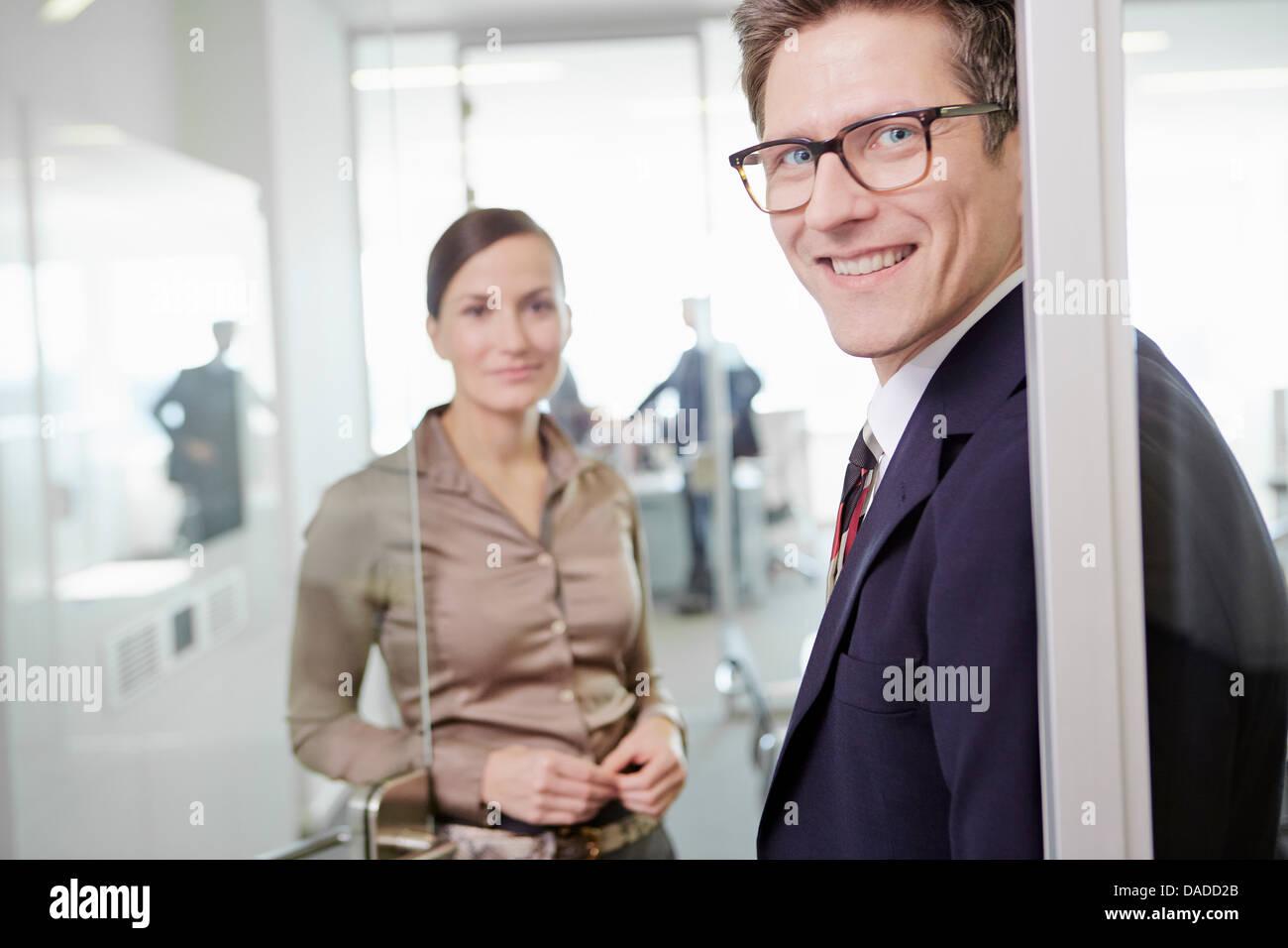 Hombre y mujer vistiendo trajes de negocios de pie en el marco de la puerta de la oficina Imagen De Stock