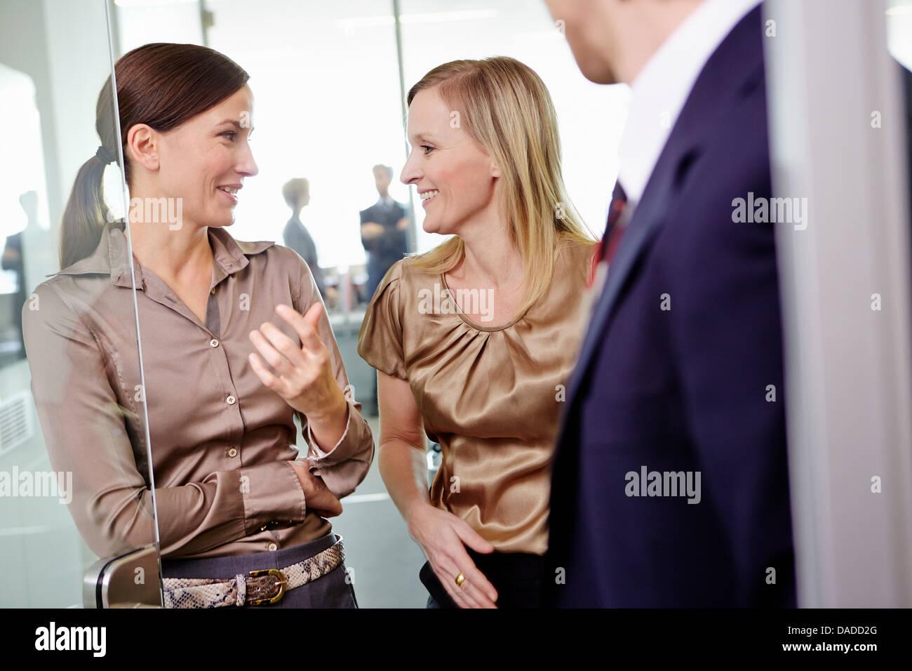 Las mujeres vestidas con atuendo de negocios de pie en el marco de la puerta de la oficina Imagen De Stock