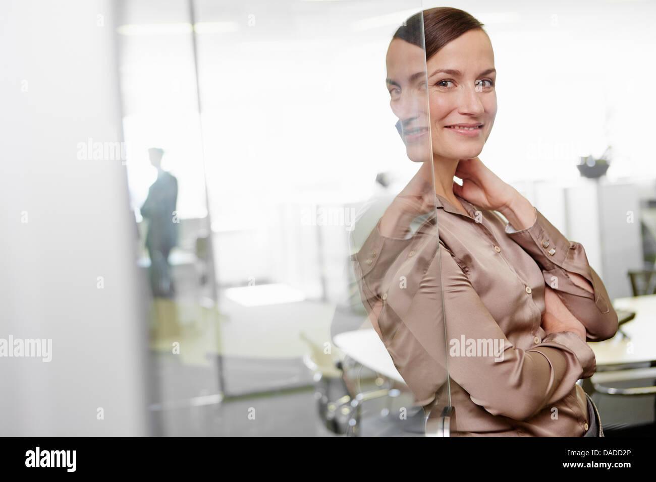 Mujer vistiendo trajes de negocios de pie en el marco de la puerta de la oficina Imagen De Stock