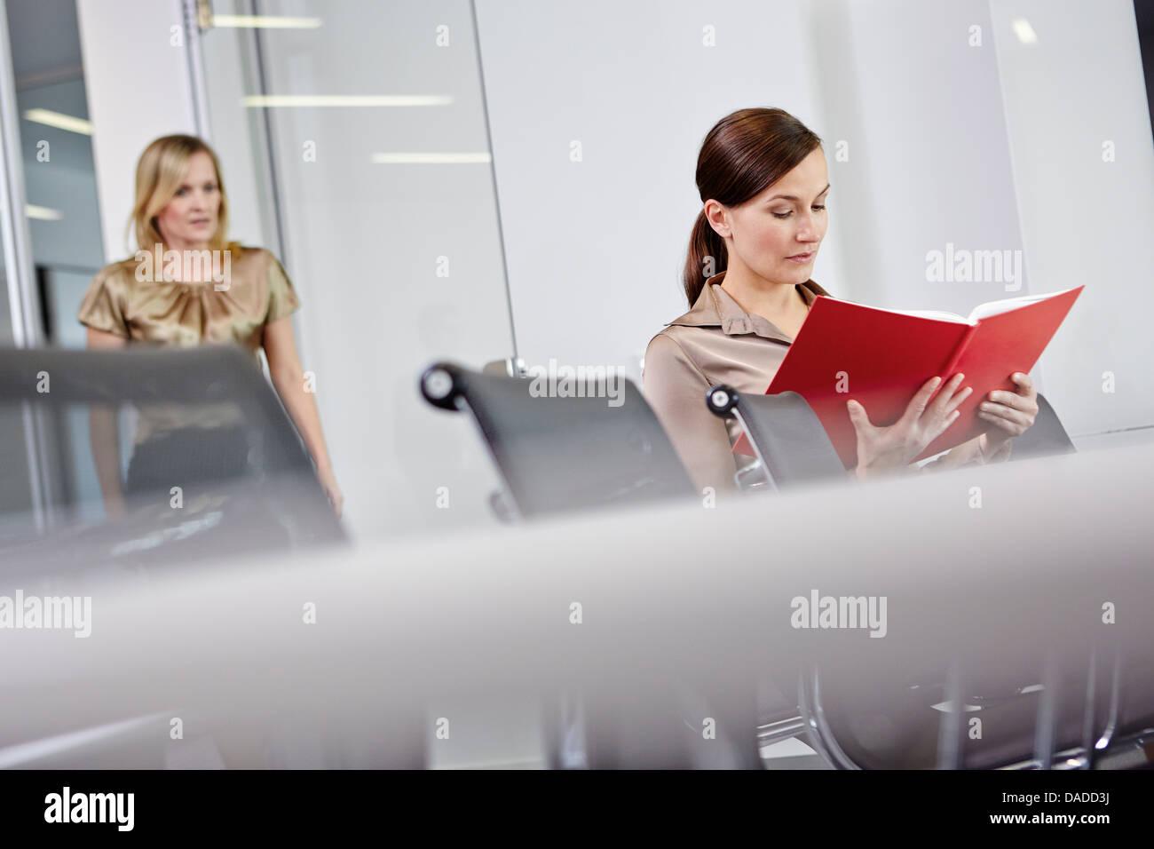 Mujer de negocios sentado en la mesa de conferencia, libro de lectura, colega acercando Imagen De Stock